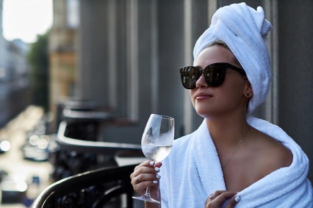 Kobieta cieszy się kieliszek szampana i widok na stare miasto na tarasie