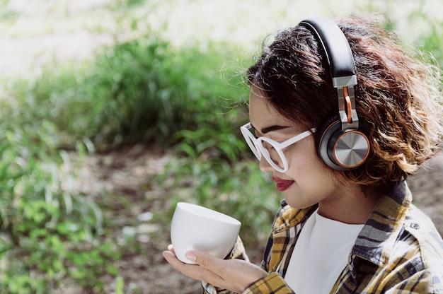 Kobieta cieszy się muzykę i pije kawę