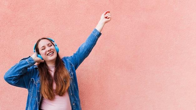 Kobieta cieszy się muzykę na hełmofonach z kopii przestrzenią
