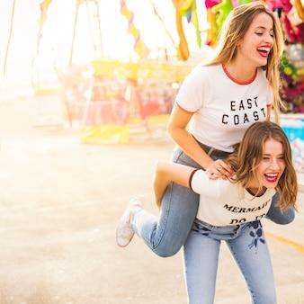 Kobieta cieszy się piggyback przejażdżkę przy parkiem rozrywki