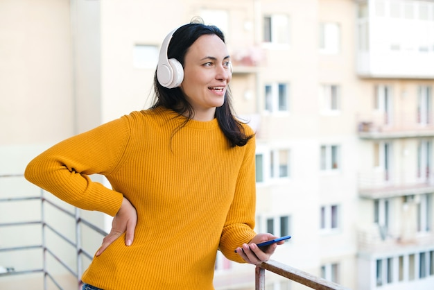 Kobieta cieszy się ranku czas przy balkonem. kobieta używa telefon komórkowego i bezprzewodowych hełmofony. samoizolacja w domu.