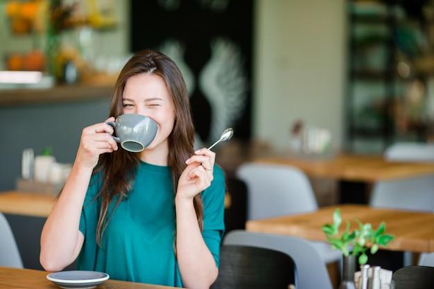 Kobieta cieszy się smakowitą kawę ma śniadanie przy plenerową kawiarnią. szczęśliwa młoda kobieta miejskich picia kawy
