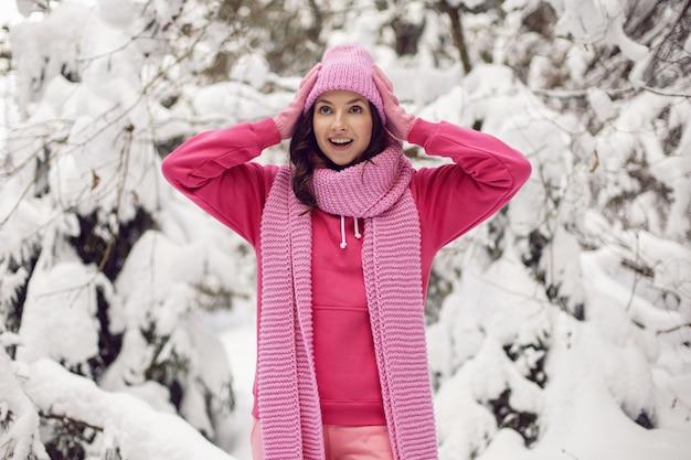 Kobieta cieszy się w różowych ubraniach kurtka, szalik z dzianiny i czapka stoi w zaśnieżonym lesie zimą