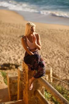 Kobieta cieszy się zmierzch na pięknej plaży