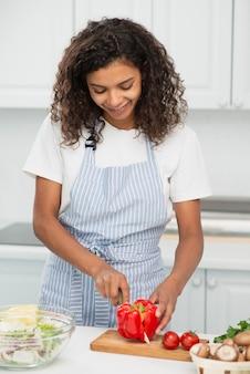 Kobieta ciie czerwonego pieprzu w kuchni