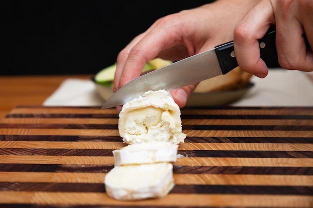 Kobieta ciie miękkiego ser na drewnianej desce