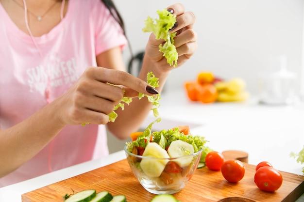 Kobieta ciie zielonej sałatki w kuchni