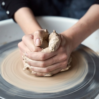 Kobieta co ceramiki na kole, ręce z bliska, tworzenie wyrobów ceramicznych. praca ręczna