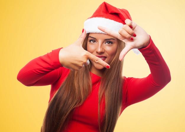 Kobieta co ramkę z jej palców w żółtym tle