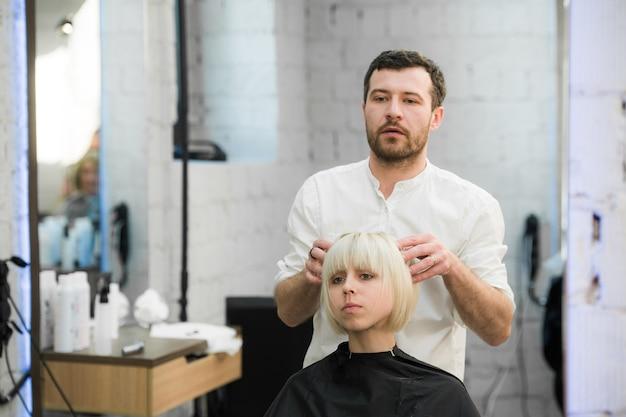 Kobieta coraz jej nową fryzurę w salonie