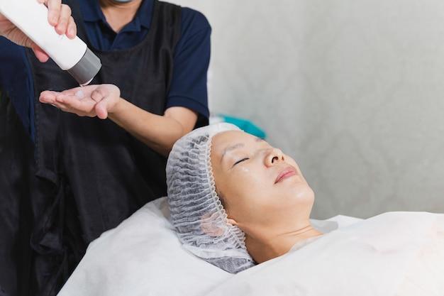 Kobieta coraz masaż twarzy w salonie kosmetycznym spa.