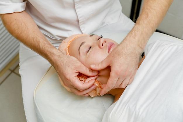 Kobieta coraz masaż twarzy. zabiegi spa w salonie kosmetycznym