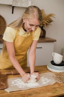 Kobieta cukiernik lub piekarz lub gospodyni domowa wyrabia ciasto w kuchni. reklama domowych wypieków