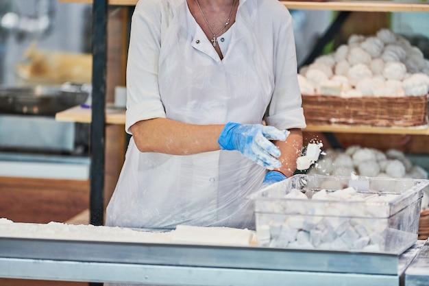 Kobieta cukiernik sprawia, że słodkie pyszne. cukiernik gotuje pastilę i sharbat - smaczna słodycz. produkcja wyrobów cukierniczych