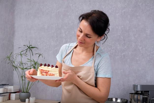 Kobieta cukiernik trzyma talerz z kawałkiem ciasta. cukiernik gotował ciasto owocowe.