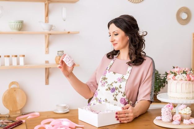 Kobieta cukiernik w domu pakuje domowe pianki w pięknych pudełkach. pakowanie słodyczy.