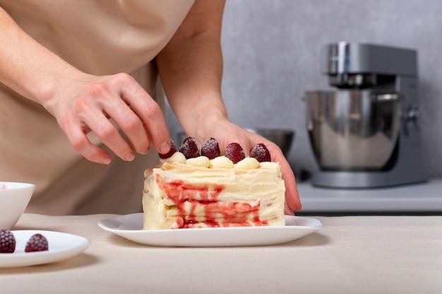 Kobieta cukiernik zdobi ciasto jagodami. tort waniliowy z nadzieniem jagodowym.