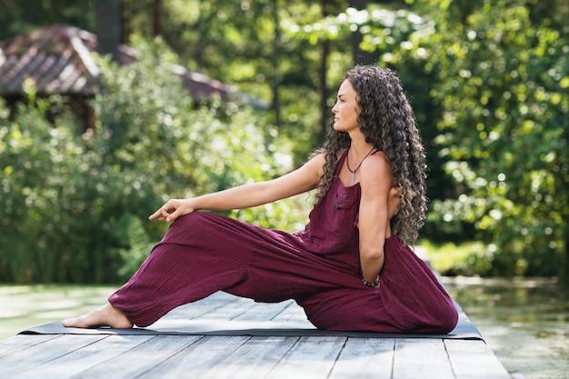 Kobieta ćwicząca jogę siedząca na macie w parku w słoneczny poranek i wykonująca odmianę