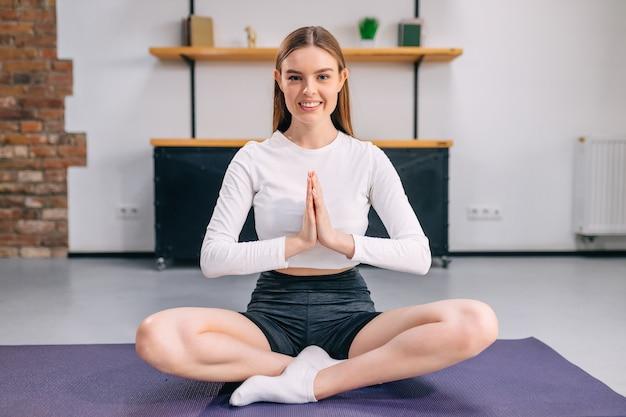 Kobieta ćwicząca jogę, siedząca w pozycji, z rękami złożonymi przed nią
