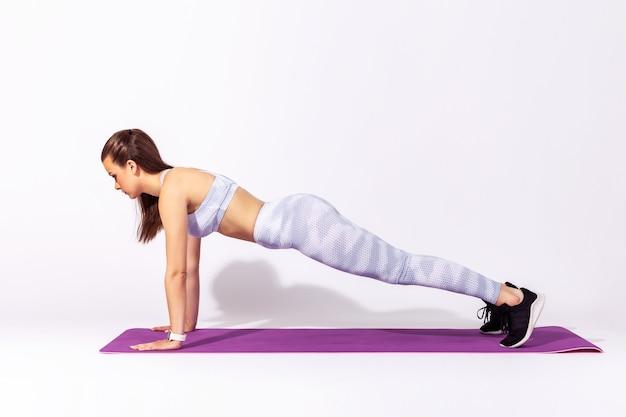 Kobieta ćwicząca jogę, wykonująca ćwiczenia phalakasana, trenująca mięśnie w pozie wysokiej deski