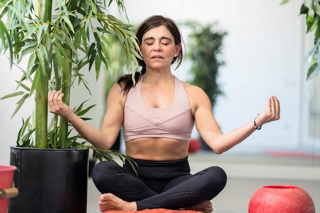 Kobieta ćwicząca jogę ze skrzyżowanymi nogami i rękami uniesionymi na boku roślin