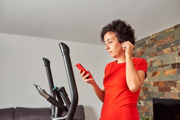 Kobieta ćwicząca na orbitreku w domu w bezprzewodowych słuchawkach sprawdzająca jej smartfona