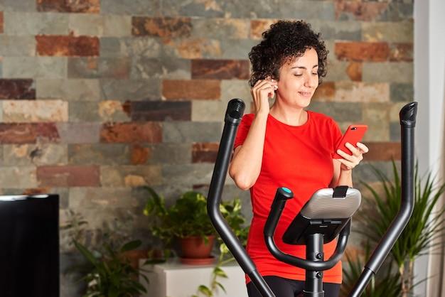 Kobieta ćwicząca w domu na treningu krzyżowym na maszynie eliptycznej przy użyciu telefonu komórkowego