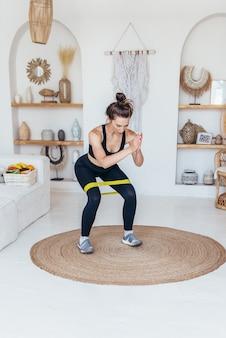 Kobieta ćwicząca w domu robi przysiady z gumką.
