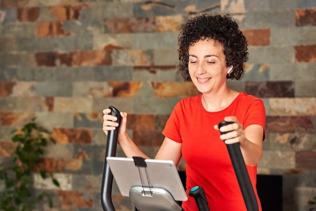 Kobieta ćwicząca w domu z lekcją eliptycznego treningu krzyżowego online