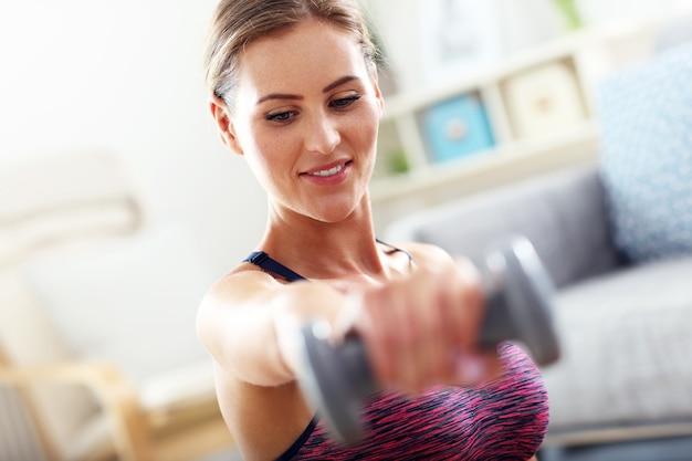 Kobieta ćwicząca z hantlami w domu