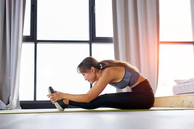 Kobieta ćwiczenia rozciągające na podłodze w domu, kopia przestrzeń. joga, pilates, ćwiczenia, ćwiczenia