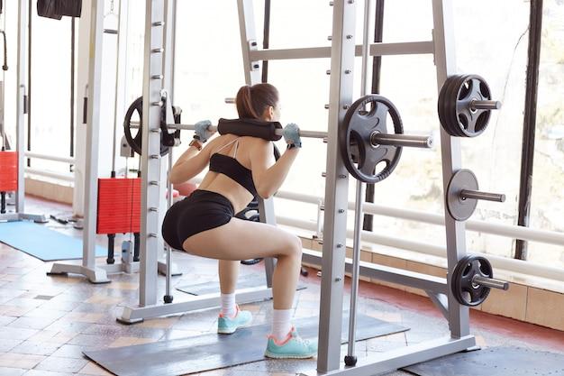 Kobieta, ćwiczenia w siłowni, model fitness fotografowane podczas robienia przysiadów z dodatkowym ciężarem na ramionach. młoda dziewczyna z kucykiem, krótkie sukienki i bluzka z dużymi ciężarami.