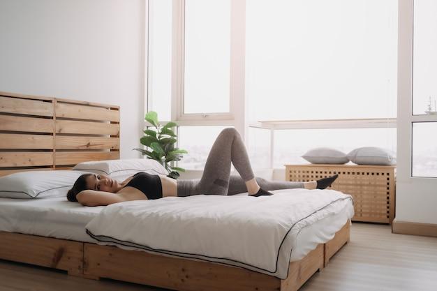 Kobieta ćwiczy chrupanie na krzyżu w swoim mieszkaniu w sypialni
