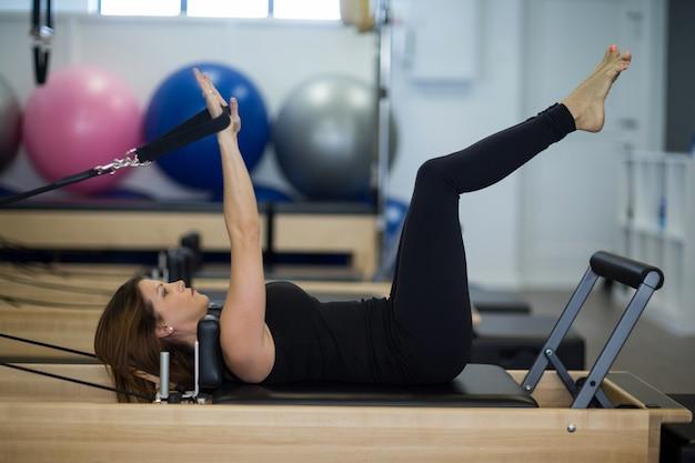 Kobieta ćwiczy ćwiczenia rozciągające na reformatorze