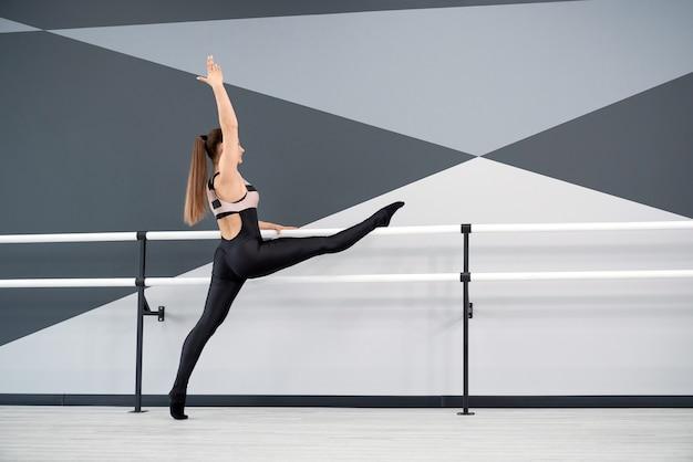 Kobieta ćwiczy dzielenie trzymając poręcze w studio tańca