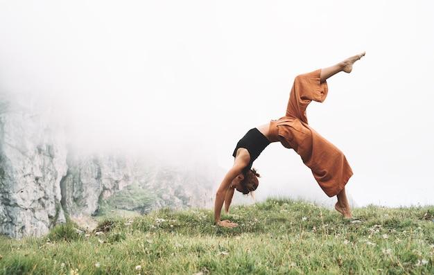 Kobieta ćwiczy jogę na łonie natury młoda kobieta robi jogę w górach