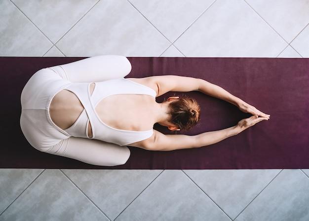 Kobieta ćwiczy jogę na macie do jogi w pomieszczeniu dziewczyna medytuje i robi relaksujące pozy jogi w domu