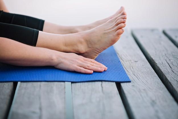 Kobieta ćwiczy jogę na świeżym powietrzu w pobliżu rzeki na drewnianym molo w godzinach porannych