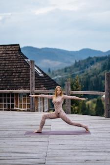 Kobieta ćwiczy jogę rano na tarasie na świeżym powietrzu.