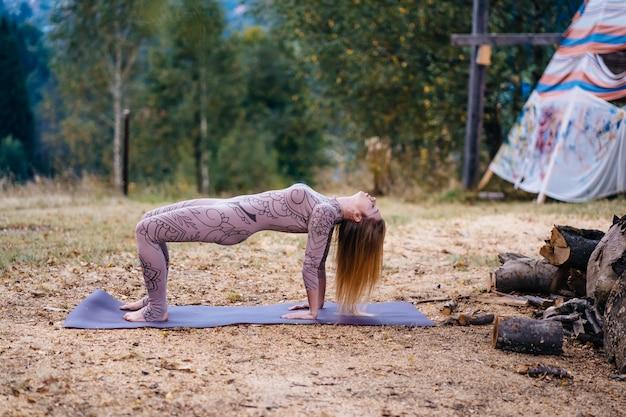 Kobieta ćwiczy jogę rano w parku na świeżym powietrzu.