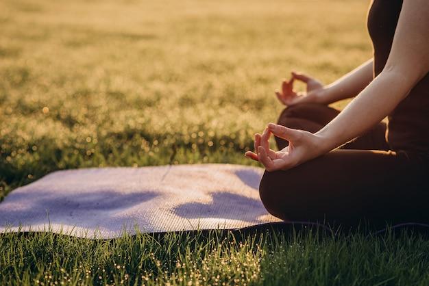 Kobieta ćwiczy jogę w pozycji lotosu wczesnym słonecznym porankiem w trawie z rosą miękka selekcyjna ostrość. skopiuj miejsce