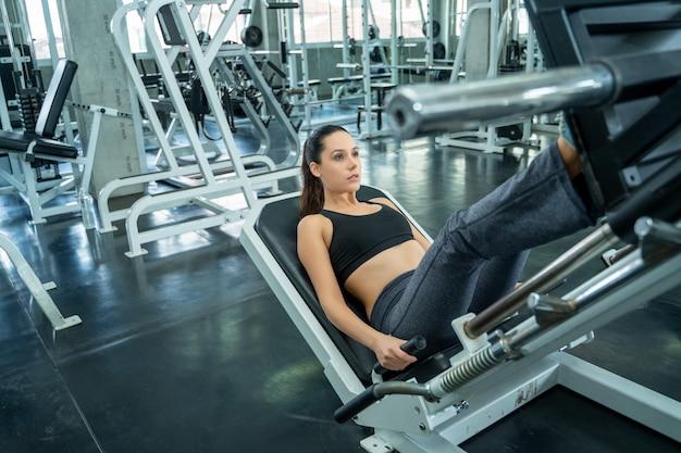 Kobieta ćwiczy mocno na gym, sprawności fizycznej kobiety stażowy trening w nowożytnej gym.