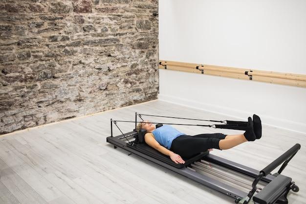 Kobieta ćwiczy na reformatorze