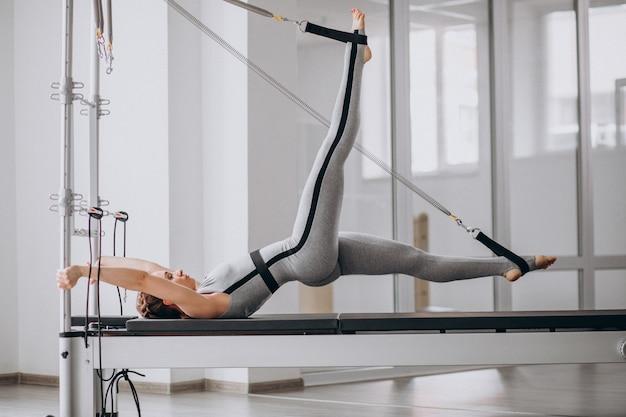 Kobieta ćwiczy pilates w reformatorze pilates