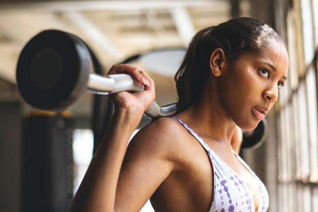 Kobieta ćwiczy podnoszenie ciężarów ze sztangą w siłowni fitness
