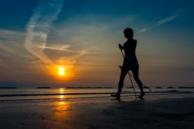 Kobieta ćwiczy północnego odprowadzenie w plaży przy wschodem słońca póżno