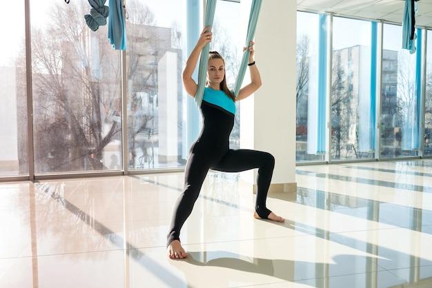 Kobieta ćwiczy powietrzną jogę w hamaku. relaksujący rodzaj sportu antygrawitacyjnego. zdrowie, mucha koncepcja jogi.