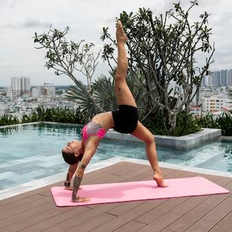 Kobieta ćwiczy pozycję jogi na świeżym powietrzu