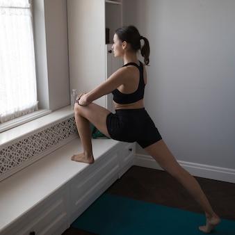 Kobieta ćwiczy przed okno