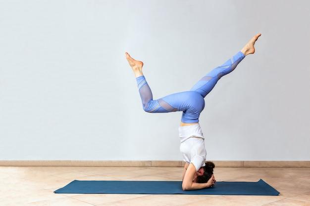 Kobieta ćwiczy przy joga studiiem w headstand
